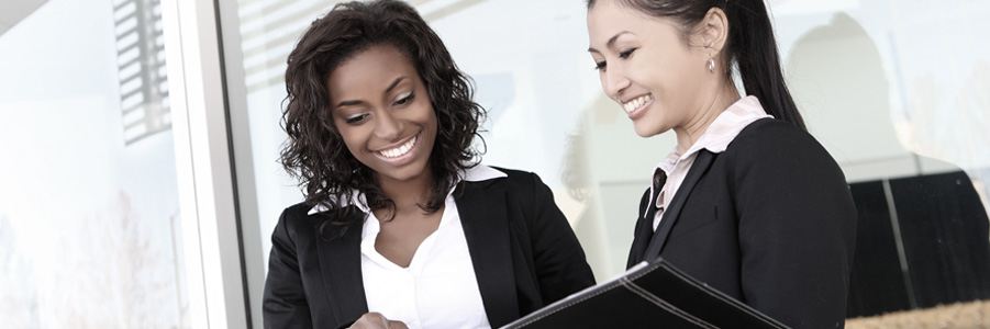 Picture of two business women smiling and looking over a recruitment portfolio